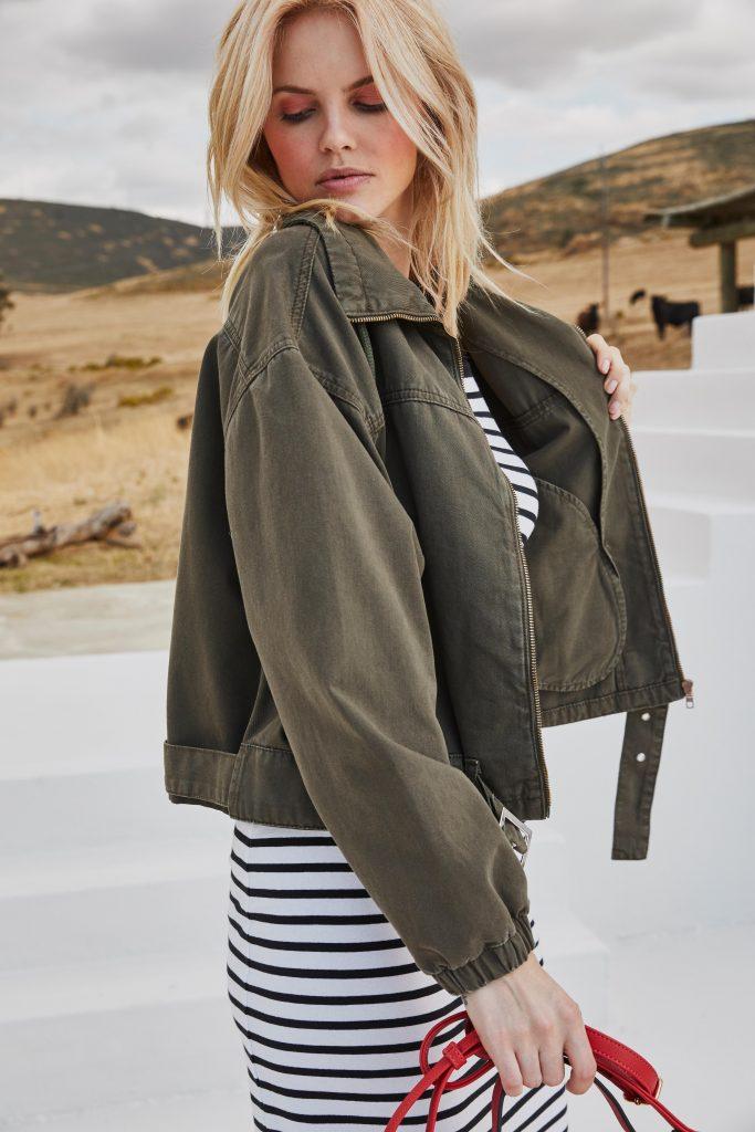 Vrouw in lente look met jas en jurk