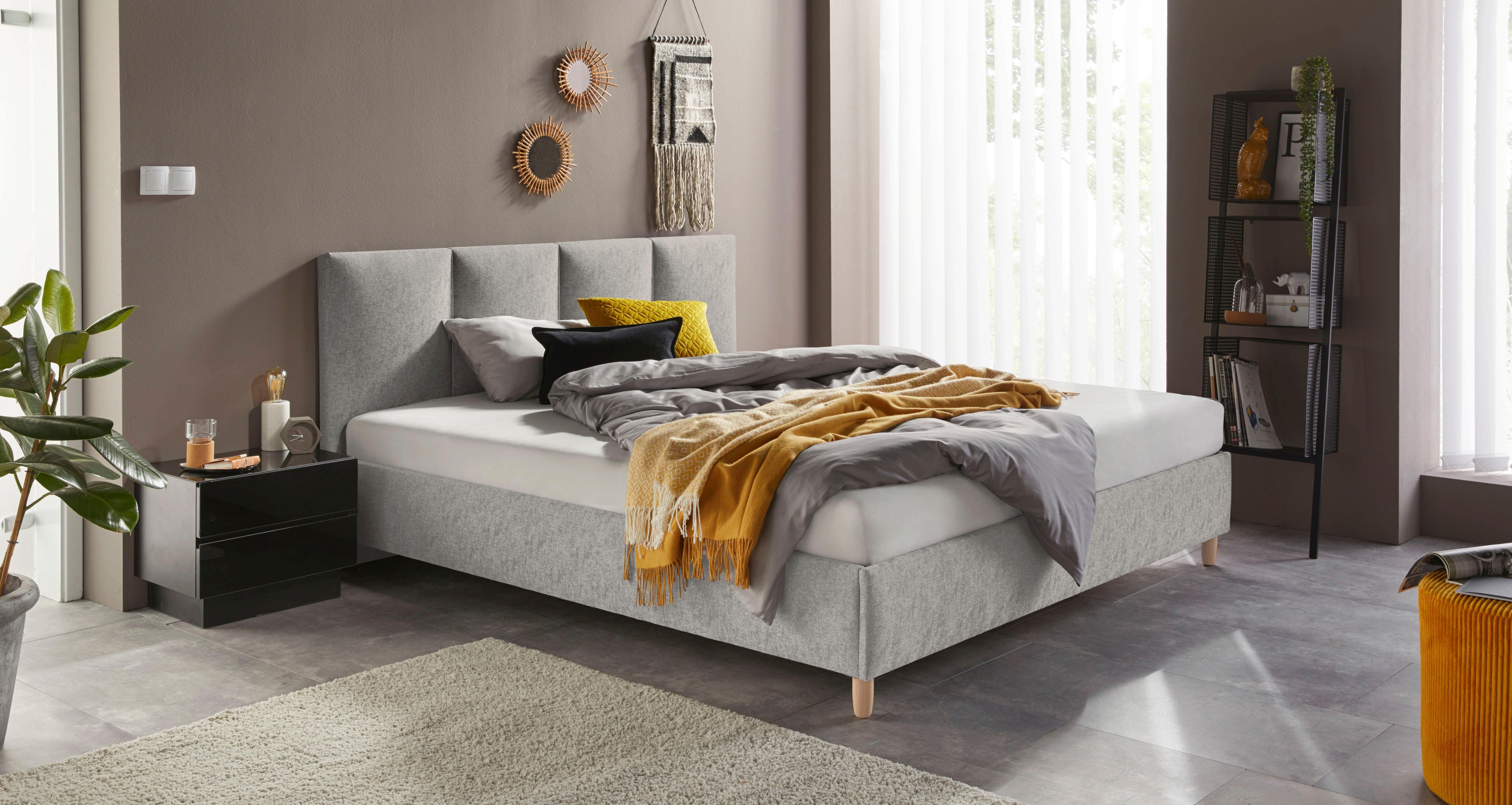 Grijs bed in slaapkamer met gele accenten