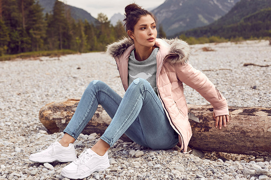Kamperen vrouw in jas en spijkerbroek buiten