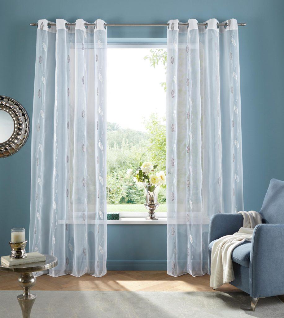 Witte doorzichtige gordijnen in blauwe woonkamer
