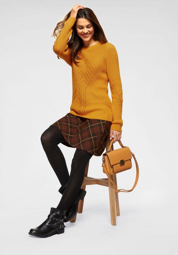 vrouw met gele trui, rode rok en maillot